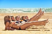 stock photo of tan lines  - Photo of several girls in bikini lying on sandy beach and tanning in the bright summer sun - JPG