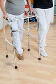 picture of zimmer frame  - Low section of woman with walker and trainer on wooden floor - JPG
