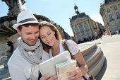 Couple standing by the Place de la Bourse with electronic tablet poster