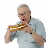 A senior man eagerly ready to bite into a giant, cream-filled cookie.  On a white background.