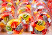 stock photo of tupperware  - Colorful natural fruit salad transparent glasses in a row - JPG