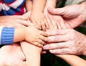 stock photo of joining hands  - Family holding hands together closeup - JPG