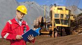 A foreman in a mining site, checking the logs in a blue folder, with a huge wheel digger in the back