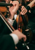 Symphony orchestra on stage, hands playing violin. Shallow depth of field, vintage style. poster