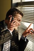 stock photo of voyeur  - Handsome business man calling on phone and looking through window blinds - JPG