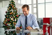 Mature business man working with xmas present and gift on desk. Successful formal businessman using  poster