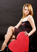 Girl In Dress Sitting Holding Red Heart