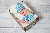 stock photo of wooden crate  - Newborn baby sleeping in a vintage - JPG