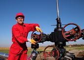 stock photo of crude-oil  - Smiling oil worker turning valve on oil rig - JPG