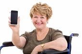 pretty elderly woman in a wheelchair showing a smart phone on white background