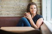 Portrait of beautiful mid adult woman with coffee mug sitting in cafeteria