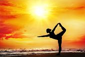 foto of natarajasana  - Yoga natarajasana dancer pose by woman in silhouette with dramatic sunset sky background - JPG
