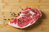 image of ribeye steak  - Aged beef ribeye steak with black and white pepper on bamboo chopping board - JPG