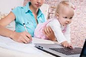 picture of telecommuting  - business woman with baby in the kitchen working with laptop - JPG