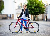 Urban leisure - young woman and bike in city