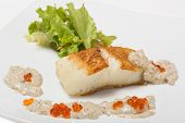 foto of halibut  - Fried halibut fillet with pepper sauce with salmon caviar and lettuce - JPG