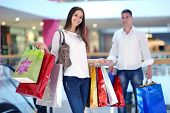 stock photo of mall  - happy young couple with bags in shopping centre mall - JPG