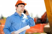 foto of power-shovel  - Architect talking at the phone in a construction site - JPG
