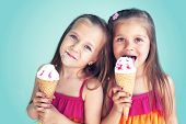 stock photo of bad teeth  - Portrait of 5 years old kid girls eating tasty ice cream over blue - JPG