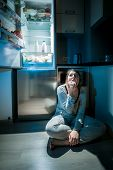 stock photo of girl next door  - Photo of woman in pajamas eating on floor next to fridge at night - JPG