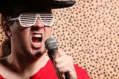 picture of crazy hat  - Crazy rock and roller singer with a big black hat party glasses in front of a cheetah skin background - JPG