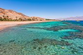 picture of aquamarine  - Aquamarine water and underwater corals along empty beach on popular resort of Eilat on Red Sea in Israel - JPG
