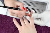 stock photo of finger-painting  - Finger nail treatment painting with brush and lacquer  - JPG