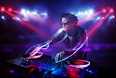 image of disc jockey  - Handsome disc jockey playing music with light beam effects on stage - JPG