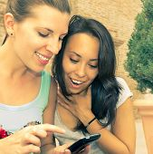 picture of two women taking cell phone  - two girls are watching funny videos on mobile phone - JPG