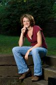 Seated Smiling Young Woman Outdoors poster