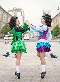 foto of irish  - Two women in irish dance dresses and wig dancing outdoor - JPG