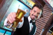 stock photo of bartender  - Freshly tapped beer - JPG