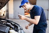 pic of lubricant  - Mechanic checking the oil level in a car engine - JPG