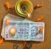 picture of laxmi  - 100 rupee bank notes and coins with indian traditional lamp - JPG