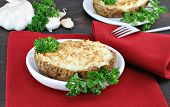 image of baked potato  - Twice baked stuffed garlic potatoes on a red napkin on a rustic wood table - JPG