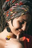 stock photo of coy  - Close up Beautiful Smiling Woman with Head Dress Leaning on the Tree - JPG