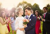 foto of blowing  - Young newlyweds enjoying romantic moment together at wedding reception outside - JPG