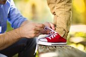 picture of tied  - Father is helping his son to tie his shoes in summer nature