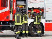 foto of ladder truck  - Italian firefighters working near the fire truck when handling an emergency - JPG