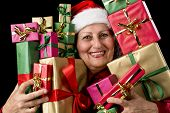 picture of gold tooth  - Cheerful elderly woman with Santa Claus hat is embosoming a host of Christmas presents - JPG