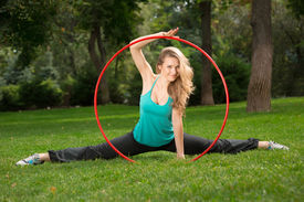 pic of hulahoop  - Young girl with a hoop sitting in the splits - JPG