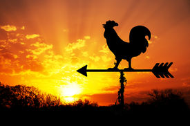 foto of roosters  - Rooster weather vane against sunrise with bright colors in clouds - JPG