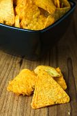 pic of nachos  - Nacho cheese flavored tortilla chips in a dark bowl on a wooden table.