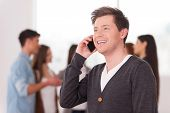 foto of people talking phone  - Handsome young man talking on the mobile phone and smiling while group of people communicating on background - JPG