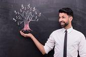 image of chalkboard  - Photo of young businessman on chalkboard background - JPG