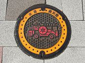 foto of manhole  - Manhole drain cover on the street at Tokyo - JPG