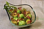 stock photo of brussels sprouts  - Grilled buttered Brussels sprouts with bacon in a glass bowl - JPG