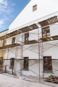 image of reconstruction  - Old building facade with scaffolding under reconstruction - JPG