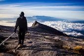 stock photo of malaysia  - A woman trekker stands at the top of Mt Kinabalu in Malaysia looking down into the clouds that sit in valley below - JPG