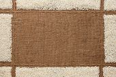stock photo of sackcloth  - Beautiful frame with rice on sackcloth with place for your text drawing - JPG